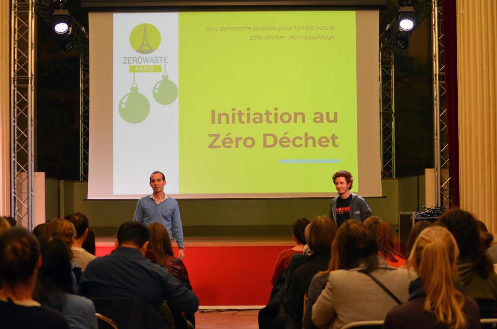 Une initiation au zéro déchet. 2 animateurs sont devant un grand écran qui affiche la 1re diapositive d'une présentation. La salle est remplie.