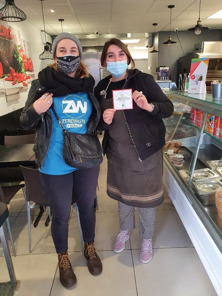 """Une commerçante tient un autocollant """"Contenants acceptés"""" à coté d'une membre de Zero Waste Paris."""