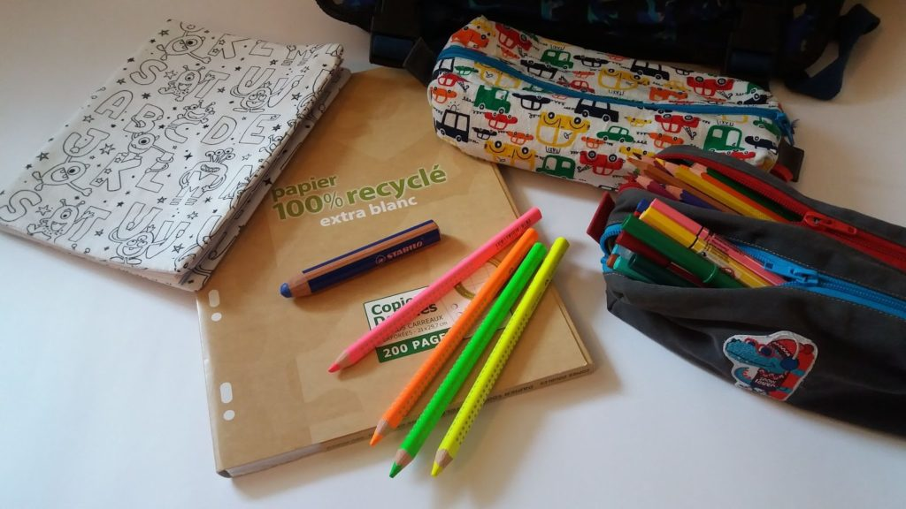 Fournitures scolaires : cahier, crayons, trousses.