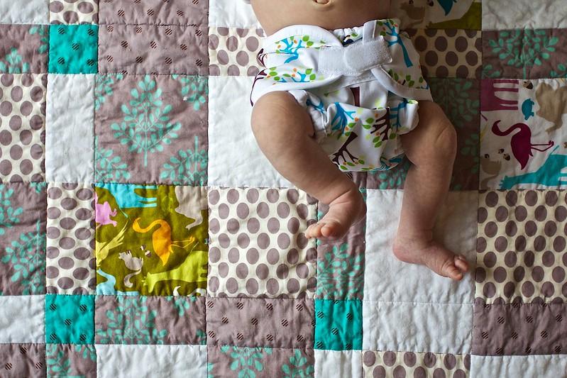Bébé avec une couche lavable sur une couverture. On ne voit que le bas du corps du bébé, le reste est hors champ.